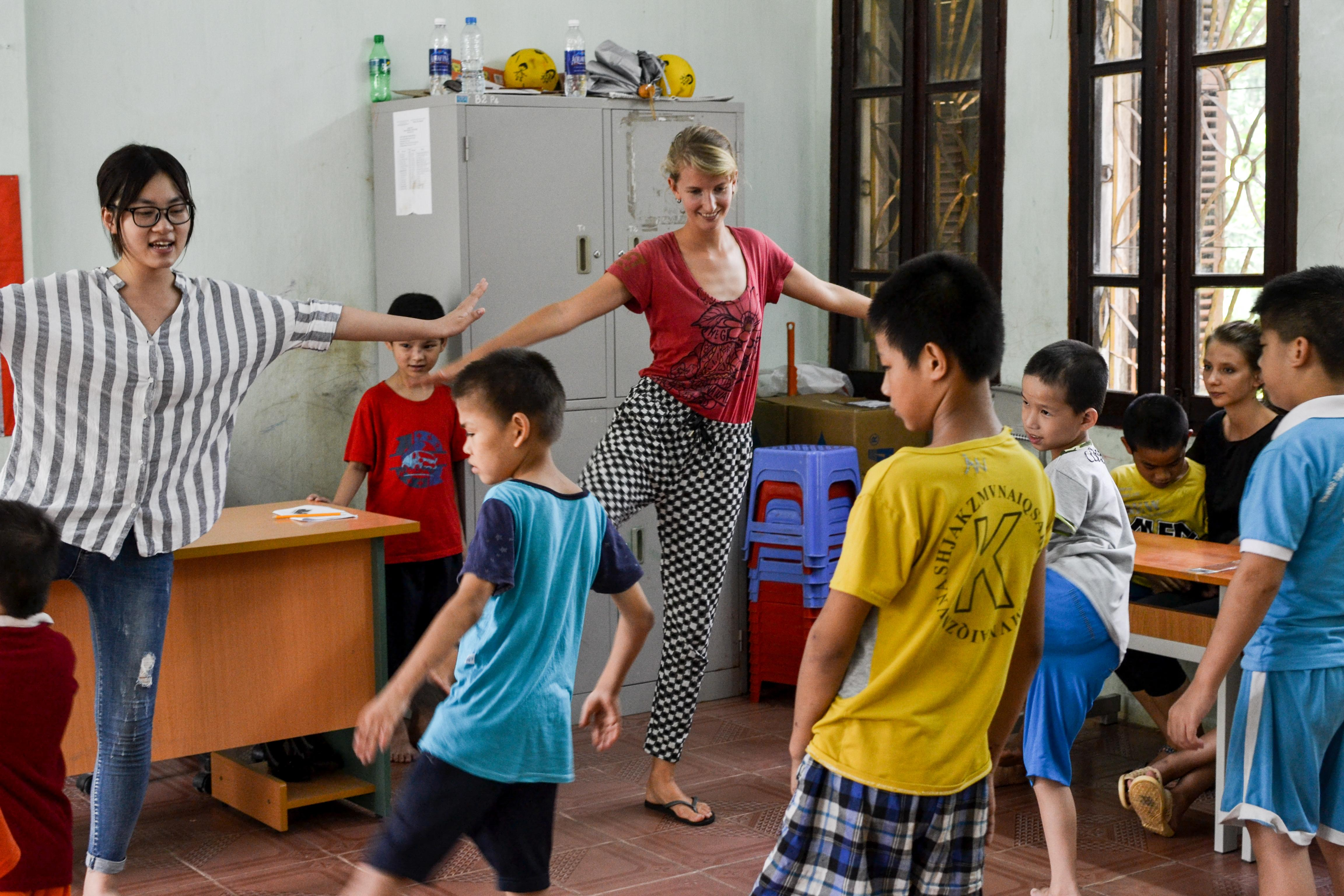 Projects Abroad volunteers demonstrate balancing exercises to a group of children at a care centre in Vietnam to develop co-ordination skills.